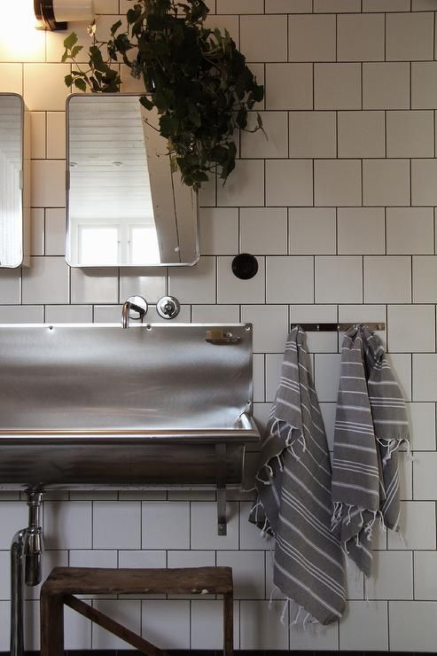 Industrial kids' bathroom features a step stool under a stainless steel trough sink and curved stainless steel medicine cabinets and mirrors next to a stainless steel hook draped in gray Turkish hand towels.