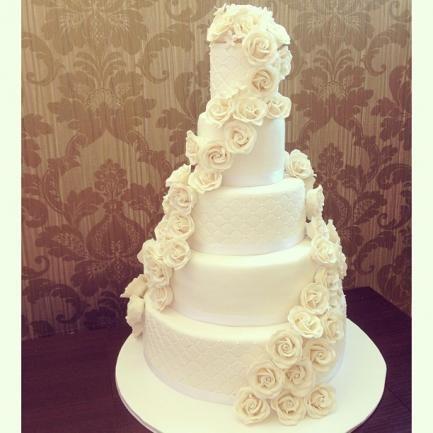 Eine Hochzeitstorte mit essbaren Rosen als Verzierung