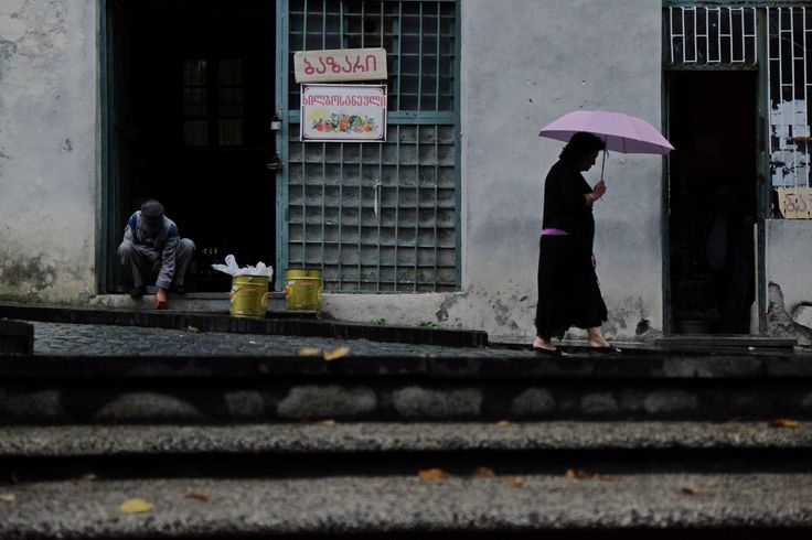 City in mountains - Signahi. Old man sells grapes.