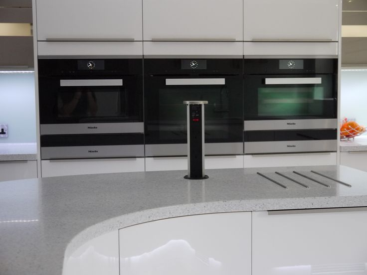 Contemporary gloss white kitchen with curved peninsular. Miele appliances, pop up socket, bi-fold wall units.