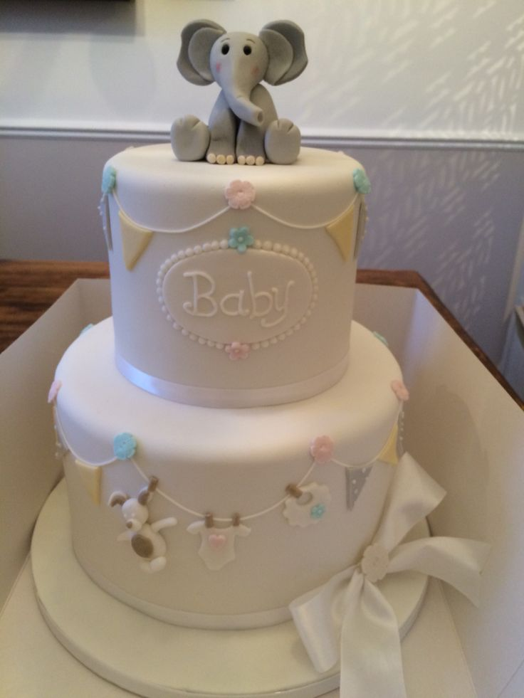 cute baby shower cake with grey yellow and white bunting and fondant elephant