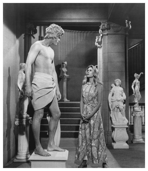 "Elizabeth Montgomery as Samantha Stephens looking at a ""living statue"" in Bewitched."