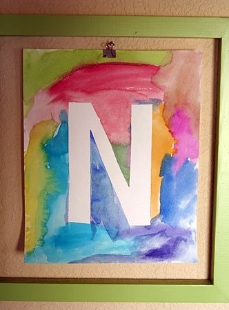 Use fita para escrever a letra inicial de um nome. Pinte com cores variadas. Espere secar. Retire a fita. O quadro está pronto