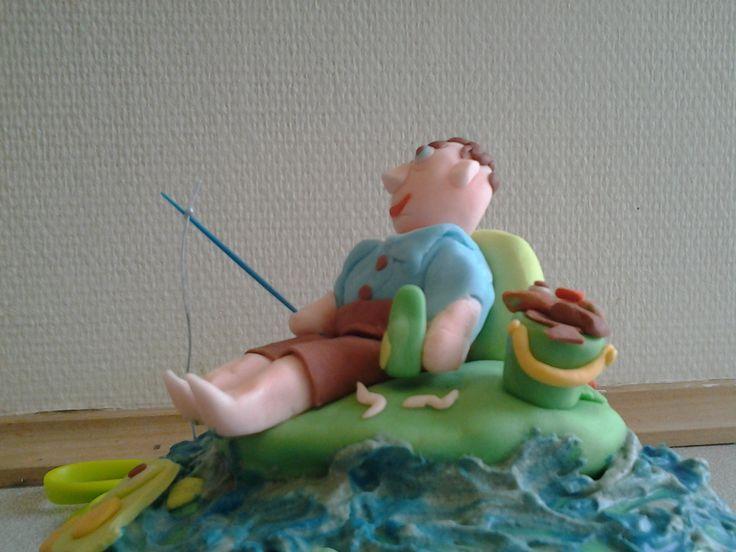 Kage der forestiller min Mand der fisker. Billedet er taget fra en anden vinkel, så man bedre kan se spanden med fisk,  ormene i græsset, øllen i den ene hånd og fiskestangen i den anden .