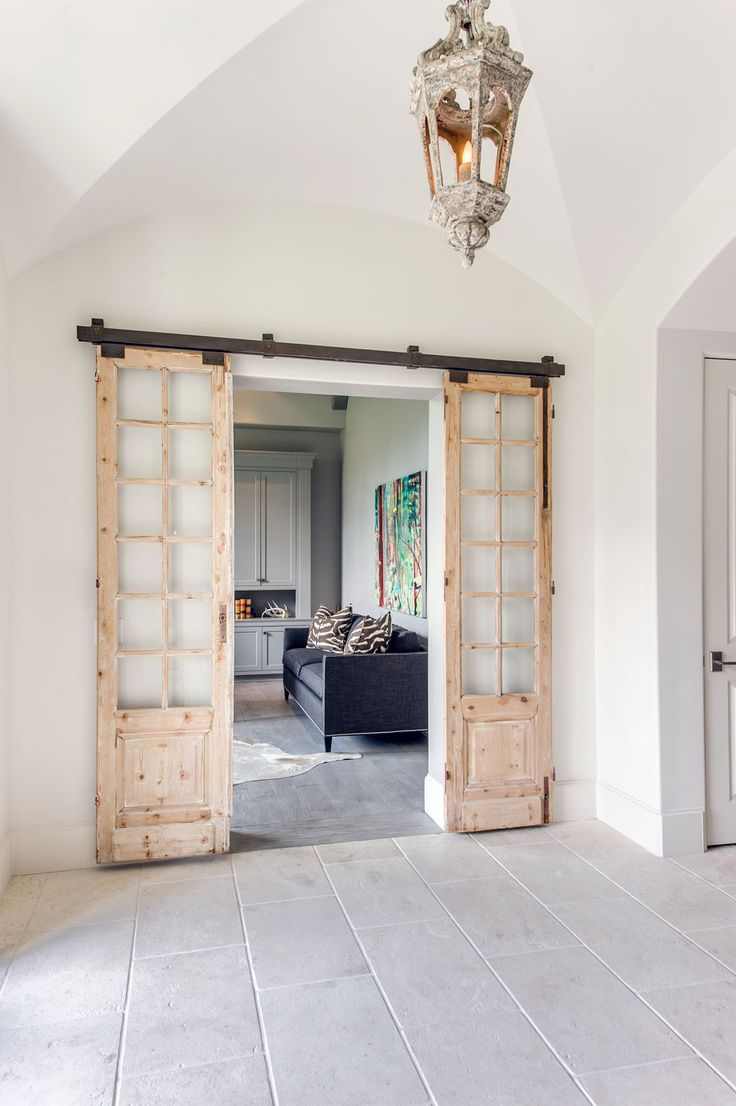 French sliding doors, found in Round Top, open to Clay's study just off the entry. The doors are hung on a metal rail and provide an excellent contrast to the smooth plaster walls, and also hint to the masculinity of the workspace inside the room.