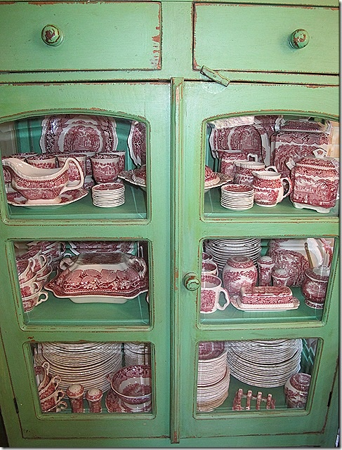 red transferware in a distressed green cupboard ~ LOVE