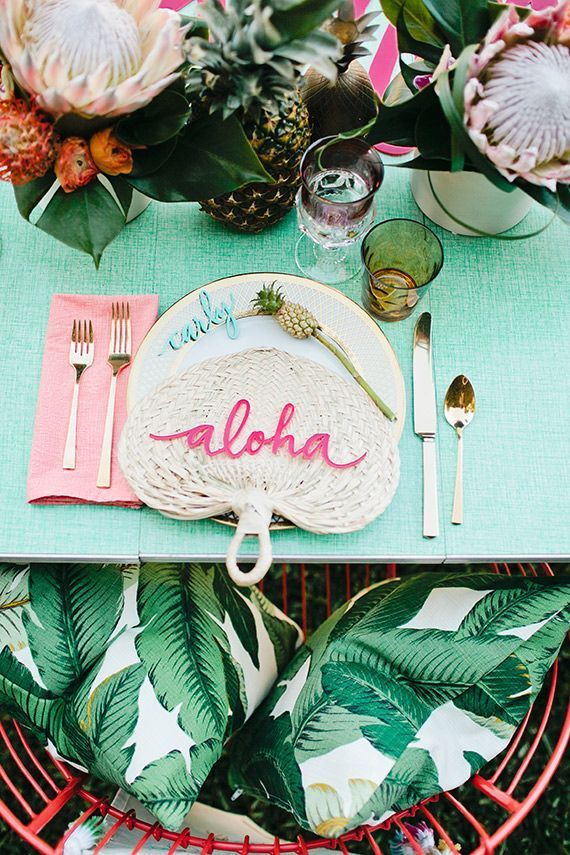 A tropical inspired summer tabletop with leafy green decor.
