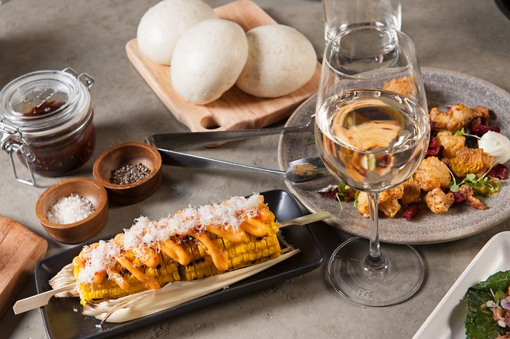 A glass of white wine accompanied with delicious corn on the cob. Only @ Junction Moama // www.junctionmoama.com.au