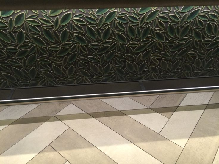 Decorative ceramic tile feature  Coloured leave pattern/textured tiles under bar , against a neutral tiled floor paired perfectly together works ideally in this space