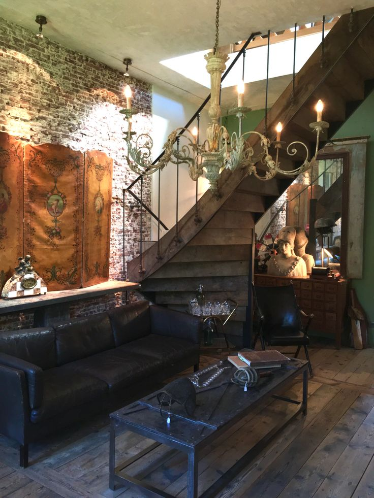 Vintage, antique, interior, living room, stair case, wrought iron table, leather couch, sculpture, chandelier, brick wall, old wooden floor