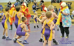 During a break at the Custer wrestling quadrangular, AAUwrestlers took to the mat to show demonstrations. Shortly after, a group of five chickens made their way to the mat to perform the chicken dance and pass out candy to the crowd.