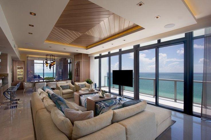grand canapé rembourré et écran tv plasma fixé à un support devant la baie vitrée