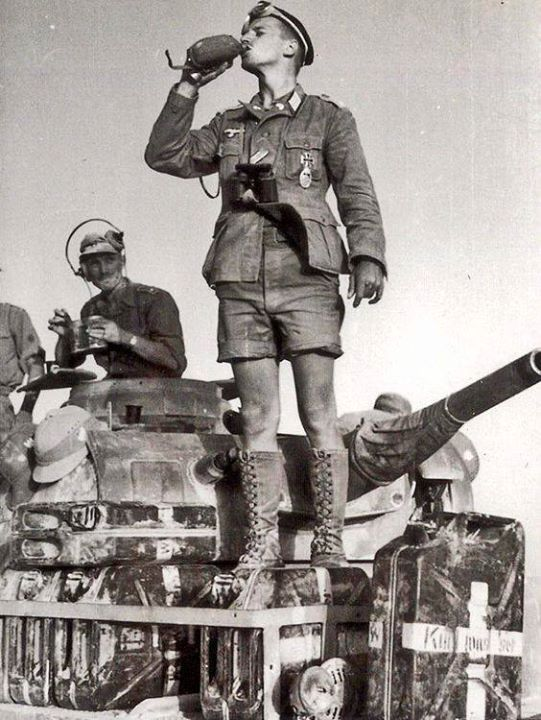 Afrika Korps soldiers with a Panzer 3 stocked with jerry cans full of water