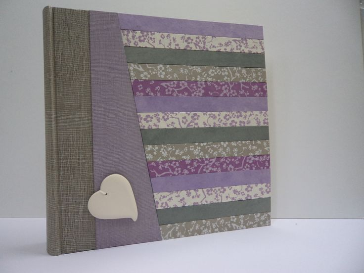 Album con composizione di carte a più colori. Cuore in ceramica bianca.