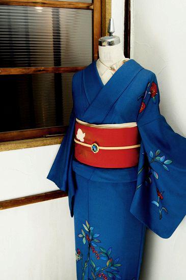 格子のような素朴な織り模様浮かぶ瑠璃紺色の地に綺麗に映える朱赤も凛と美しく、椿と南天の枝葉が染め出された袷の付下げ着物です。