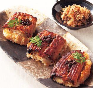 鰻のふっくら加減に驚き!絶品です。  [竹茂楼]鰻おこわ  18世紀前半に美濃(岐阜県南部)から京都へ移り、茶屋を始めたのが「美濃吉」のはじまり。現在、その京都本店は、1992年に建てられた数寄屋造りの京懐石「竹茂楼」として知られています。その川魚料理の老舗の技が反映された名品が、「鰻おこわ」。甘辛たれで付け焼きにした大ぶりの鰻をおこわの上にのせ、竹の皮で包みました。鰻はていねいに骨抜きされているので、骨の心配なくいただけます。白蒸し、黒米おこわ、赤米おこわの3種1セットで1人前。京都らしい湯葉ちりめんも詰め合わせました。ご飯のお供としても重宝します。  【編集部からひとこと】 蒸し方とお米の違いで3種類。ふっくら焼き上がった鰻は温めると甘辛い香りがぷうんと立ち上ぼります。料理屋らしい味へのこだわりが感じられます。