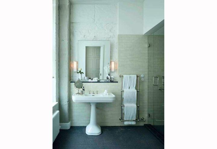 Berliner Loft. Badezimmer mit klassischem Waschbecken, sichtbarer Wand und ebenerdiger Dusche