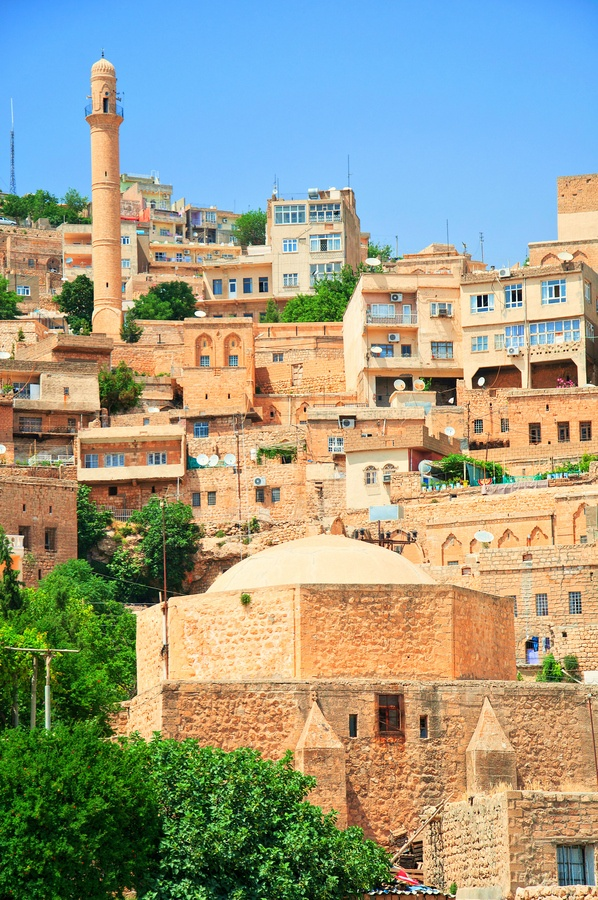 """Mardin: """"Mardin is 96km south of Diyarbakır. As you approach from the north, the modern town now sprawls unattractively over the hill before you can see why you have come here, but be patient. You must continue right up on to the rocky crag where old Mardin sits. Only then do you begin to catch glimpses of the beautiful stone-carved and decorated mansions, Arab-style, which are Mardin's real attraction."""" Eastern Turkey: the Bradt Guide; www.bradtguides.com"""