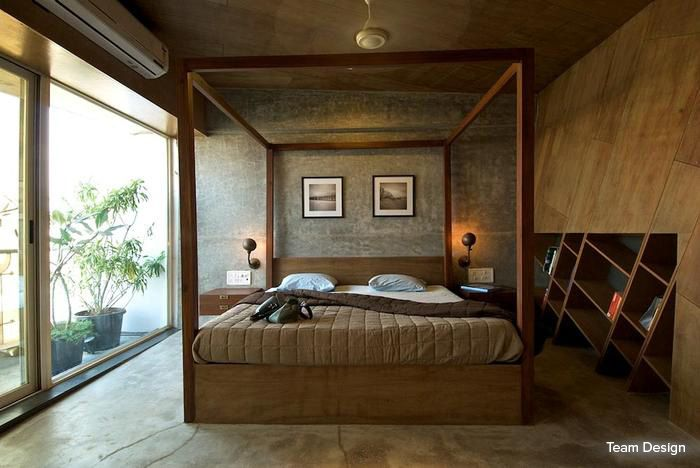 Potted plants, a wooden poster bed and an innovatively designed bookshelf, this earthy  bedroom provides a respite from the fast-paced city life #bedroom #homedecor #brown #contemporary Design Courtesy - Team Design, Mumbai