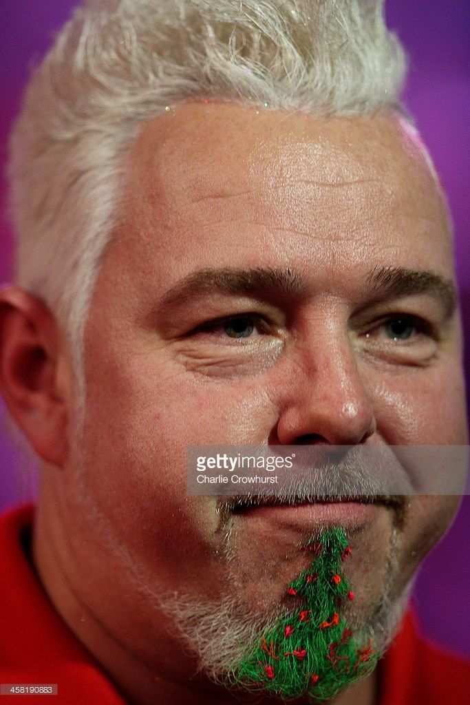 Peter Wright of England, wearing a Christmas tree beard, looks on after winning his second round match against Per Laursen of Denmark during the Ladbrokes.com World Darts Championship on Day Eight at Alexandra Palace on December 20, 2013 in London, England.