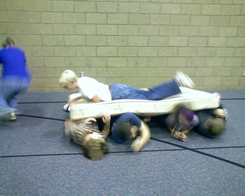 "Youth Group Game: Mattress Surfing Race.  Split everyone into teams of 5-8,each with a mattress. One person is the surfer, everyone else are ""rollers."" Line teams at one end of a large room.  Rollers lay side-by-side underneath that mattress with the surfer on top. When you start the race, all the ""rollers"" roll together toward the opposite end of the room, without losing their surfer.  Roller at end runs back to front so the mattress doesn't drop.  First over finish line wins."
