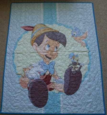 Australian Handmade Gifts - Pinocchio Cot Quilt - $75 - https://www.highlandshandmade.com.au/pinocchio-cot-quilt-75/ - Pinocchio  Panel depicting the loveable rascal.  100% cotton front and backing fabric with lightweight wadding.  Machine quilted with heart shapes.  Washable with a gentle cycle.  Suitable for a little boy.  Size 108 x 87 cms.  Made in Moss Vale in the Southern Highlands of country NSW by Dennis Buck.  Time taken to make was 6 to 8 hours.
