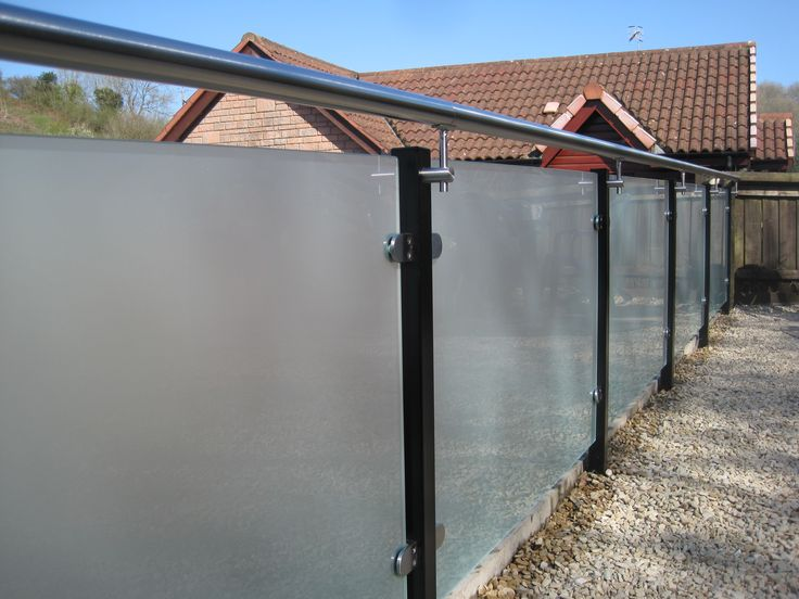 Opaque glass balustrade design with stainless steel handrails and fittings and black upright posts.