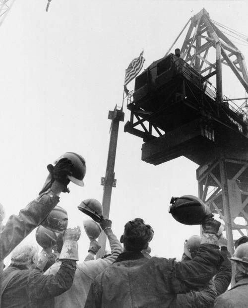 December 23, 1970~ Construction Workers raise their hats in salute as the American flag is attached to a steel column which is hoisted to the top of the North Tower building of the World Trade Center