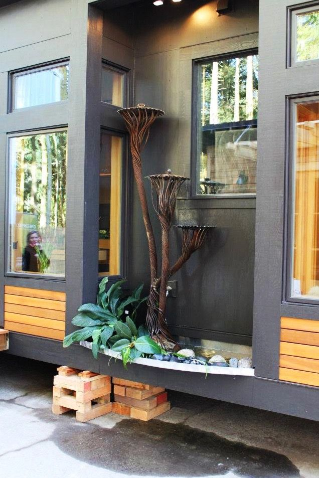 Interesting outside feature on this is the 450 sq. ft. Waterhaus Prefab Tiny Home designed by GreenPod Development and built by Sprout Tiny Homes. From the outside, you'll notice it has an elegant, clean, and modern design.