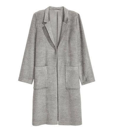 Graumeliert. Knielanger, offener Mantel aus weichem, gefilztem Stoff mit schmalem Revers. Der Mantel hat aufgesetzte Vordertaschen und seitliche Schlitze.