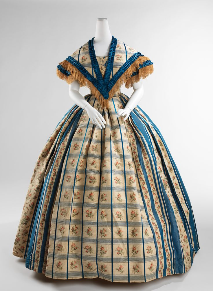 "Evening Dress (with Pelerine): ca. 1857-1860, American, silk. ""The female silhouette of the middle of the 19th century consisted of a fitted corseted bodice and wide full skirts. The conical skirts developed between the 1830s, when the high waist of the Empire silhouette was lowered and the skirts became more bell shaped, to the late 1860s, when the fullness of the skirts were pulled to the back and the bustle developed..."""