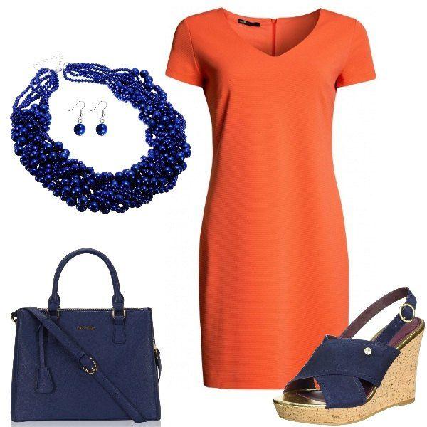 Un vestito dal taglio semplice, di una bella tonalità di arancio viene abbinato al blu delle scarpe con zeppa, della borsa a mano con tracolla e della parure, composta da una collana a più giri di perline e dagli orecchini con pendenti.
