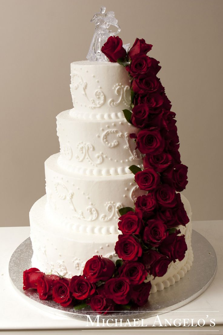 Fresh Red Roses #21Floral This four-tier buttercream cake is decorated with an ornate swirl and fresh red roses that are cascading down the cake.