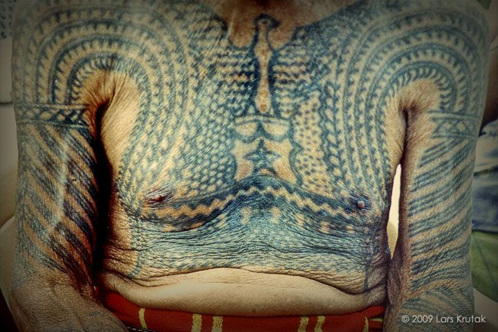 Lakay Dilag wears a very intricate bikking or warrior's chest tattoo. Traditionally, these V-shaped markings represented the gayang or eagle: an oracle bird and messenger to the Creator God Kabunian. However, this once abstract motif has been accentuated and replaced with a figurative rendition of the eagle that many WWII Kalinga veterans borrowed from peso or centavo coin designs from the American commonwealth period (1935-1946). The star (bituwon) beneath the eagle symbolizes the beacon or…