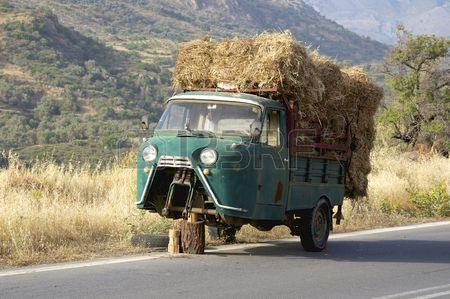 Defecte oude drie wielen vrachtwagen met hooi lading op de weg op Kreta De Truck is op de weg naar R Stockfoto