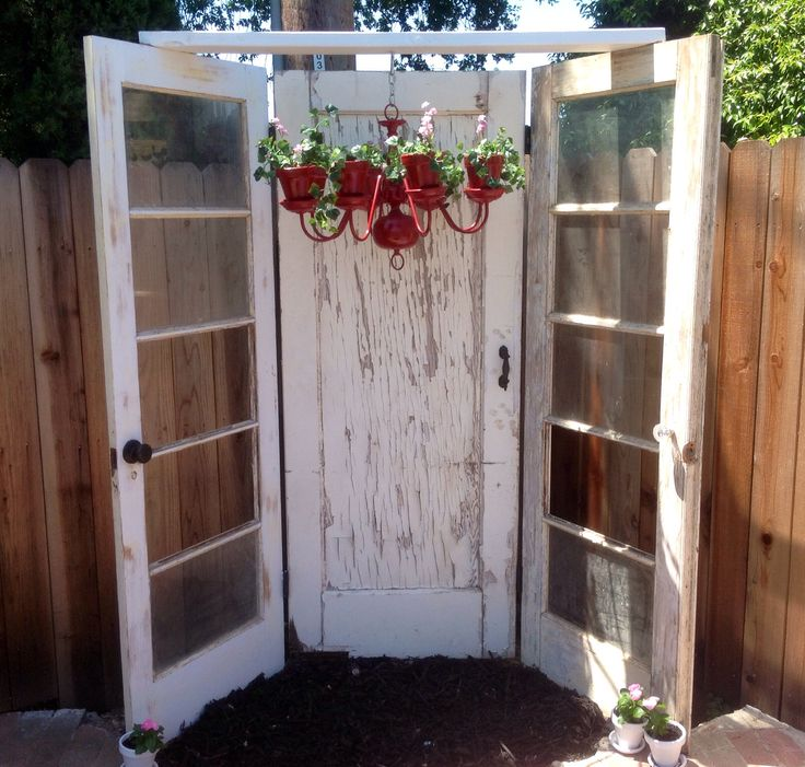 """Thank you Pinterest for the ideas!  I found the two side doors at a barn sale for $5 each and the middle door on Craigslist for cheap! I added """"dummy door knobs"""" to all.  My son hinged them together for me and added the board across the top so that I could hang my chandelier turned into planter ( also found on Pinterest).  We also added solar lights to the back of the piece in the middle, so at night it lights up beautifully."""