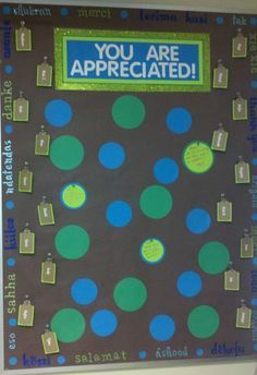 """Employee Appreciation Board! Around the edges are """"thank you"""" in various languages. Down the sides are tags with every employees name on it, and a binder clip attached behind it. The tags are two fold, 1) to remind everyone that they are appreciated and 2) to attach fun goodies to. The dark green and blue circles are permanently attached. The lighter green circles are what people write their personal notes on to say THANKS! This just went up, we'll see how it goes over!"""