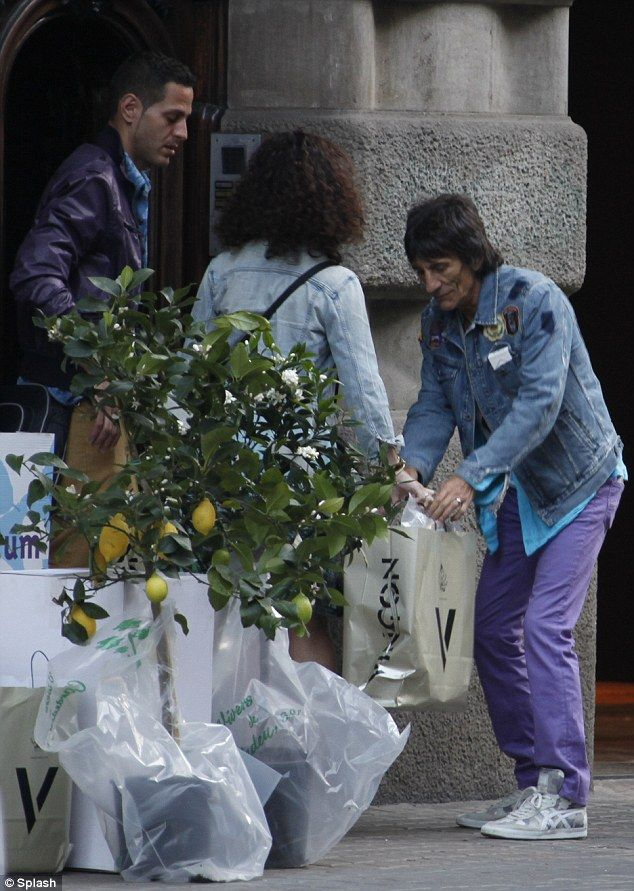 Rolling Stones' Ronnie Wood settles into new Barcelona home with wife Sally Humphries. Pictured in Barcelona (Catalonia) on Sunday, the pair cut domesticated figures as they shopped locally for everyday essentials and furniture. March 2014
