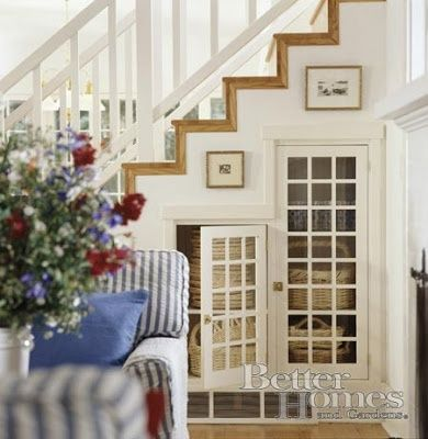Attractive doors and shelving lend a better way to convenient storage. Fill with baskets or books for clean lines.  Another creative use for under-utilized under the stairs storage space.  See more ideas on our facebook page at www.facebook.com/gardnerteam