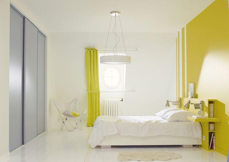 Les rayures blanches verticales asymétriques pour couper le mur jaune. Une tête de lit déco et pratique pour la chambre