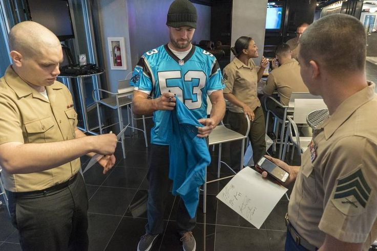 Panther linebacker Ben Jacobs signs autographs for Marines Chad Prather, left, and Edward Gentry. The Carolina Panthers hosted military personnel for a live video game competition between Carolina Panthers players and troops. Video games were played in Bank of America Stadium's Grid Iron Club. The Panthers partnered with the USO of North Carolina and Pro vs. GI Joe to provide this event.
