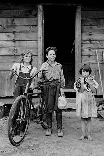 Three of the four Arnold children. The oldest boy earned the money to buy his bicycle. Western Washington, Thurston County, Michigan Hill.