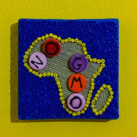 """Shop: Canvas D'Afrique - No GMO. This Africa is partially beaded on canvas in blue and yellow with a center of textured grey fabric and large beads spelling out """"No GMO"""". Size: 10cm x 10cm. By Beadoir D'Afrique"""