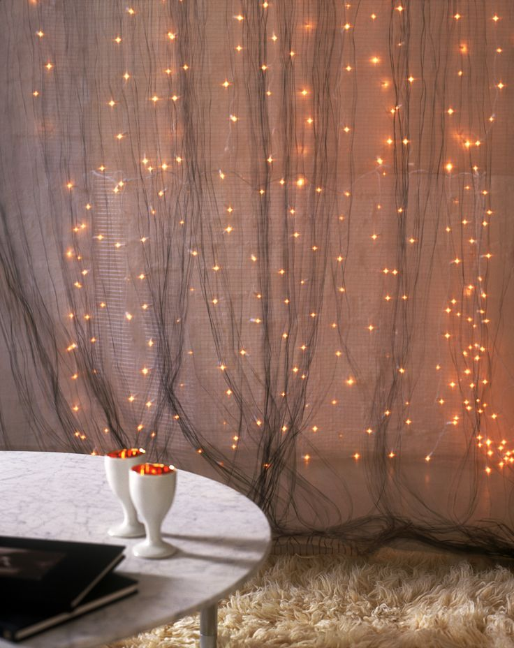 Unisci più fili di luci di Natale per creare una tenda di luce impalpabile, puoi sovrapporla alle tende della sala oppure crearne una nuova su una parete vuota della stanza  -cosmopolitan.it