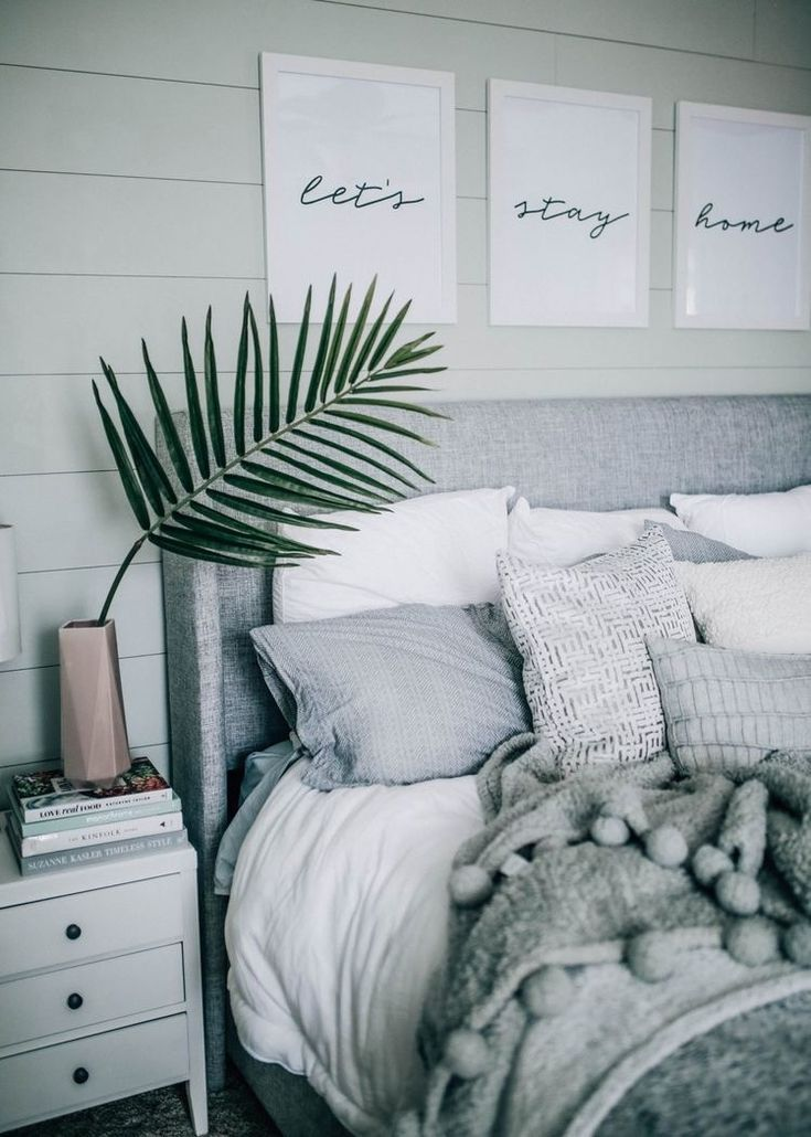 Simple, striking bedroom in white and gray with simple decor: printable word art in white frames and a palm frond.