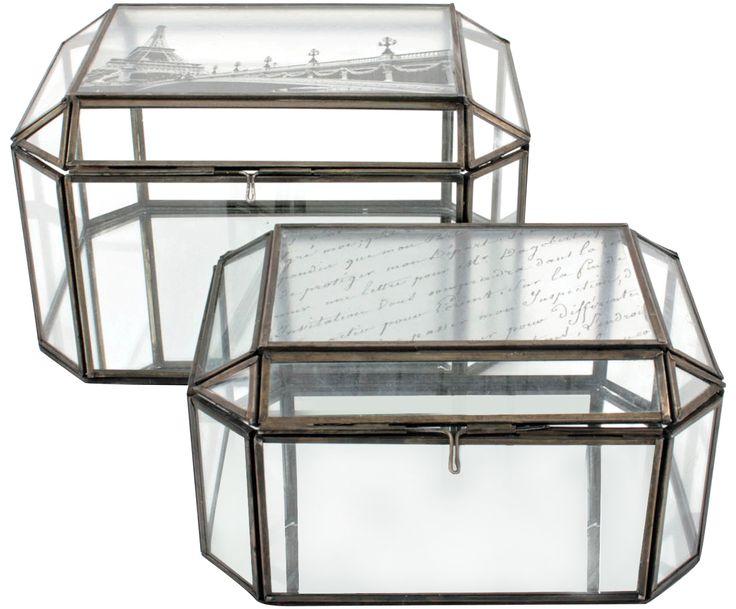 Das 2-teilige Glasboxen-Set TREASURE besteht aus Glas, das mit Metallstreben ummantelt ist. Dadurch erhalten die beiden Boxen einerseits einen robusten wie andererseits auch filigranen Touch. Diese Mischung ist es, die das Boxen-Set zu einem tollen Deko-Objekt werden lässt.