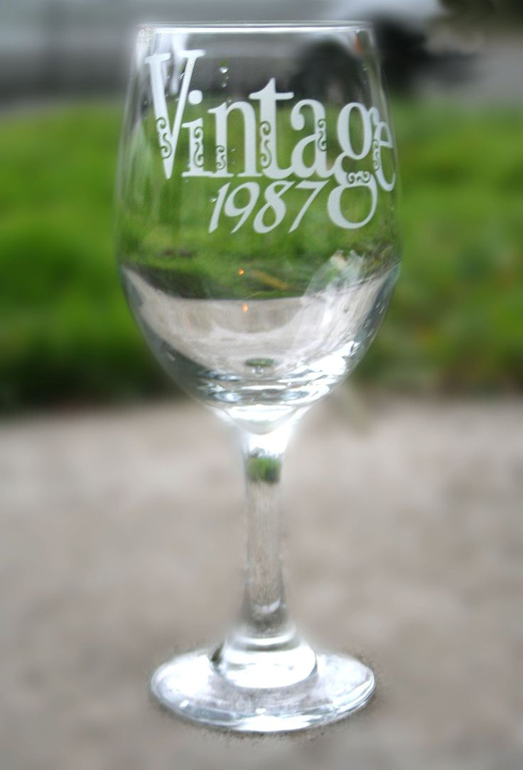 """30th Birthday Wine Glass, Hand Engraved with """"Vintage 1987"""" and Optional Personal Message on Foot of Glass. Your wine-enthusiast buddy is one a kind. Celebrate their big 3-0 with this beautifully hand-engraved glass that reads """"Vintage 1987"""". Each letter in the word """"vintage"""" is entwined with curls, giving the glass is own unique elegance. """"1987"""" can be changed to any year you'd like and is written in sassy italics. The foot of a glass reads an optional personal message to your birthday…"""