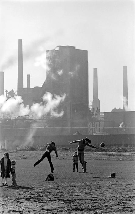 David Hurn UK. Wales. Cardiff. Children play football in spare land in front of East Moors steel works at the time that the steel works were closed. Perhaps their fathers are now out of work....