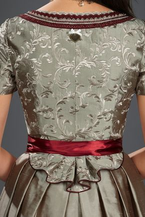 Einzigartig und extravagant ist das AlpenHerz Dirndl Jana. Die Ärmelchen und das Schößchen des Dirndls schmeicheln jeder Figur. Am Mieder aus exklusiv bestickter Seide in sand/gold werden durch die aufwendige Borte und die Brosche am Ausschnitt nochmals Details gesetzt. Die Schürze ist mit einem Blumenmuster aus Perlen veredelt und setzt einen weiteren Akzent an dem Designerdirndl. Auch dieses Modell wird ohne Bluse getragen.