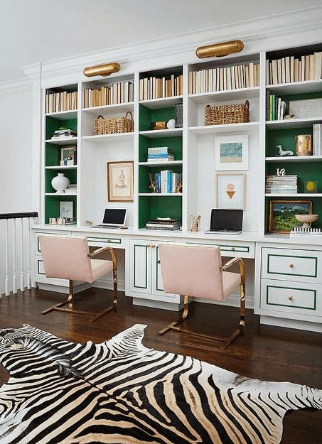 feminine home office with emerald green accents, pantone lush meadow, soft pink office chairs, zebra print rug, dark wood floors, white walls, gold details, glam interior design